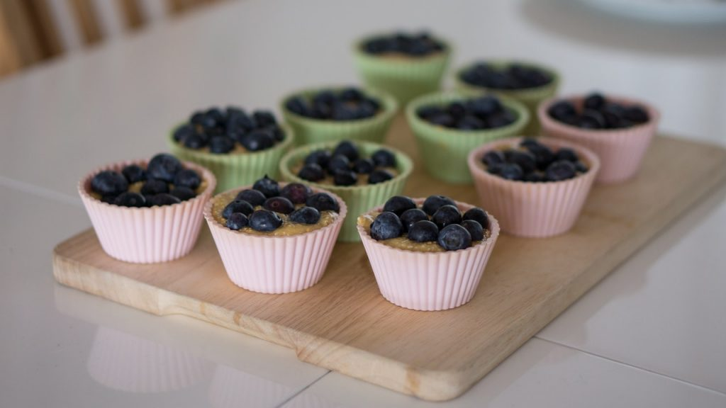 Blueberry muffins cooling on a wood cutting board.