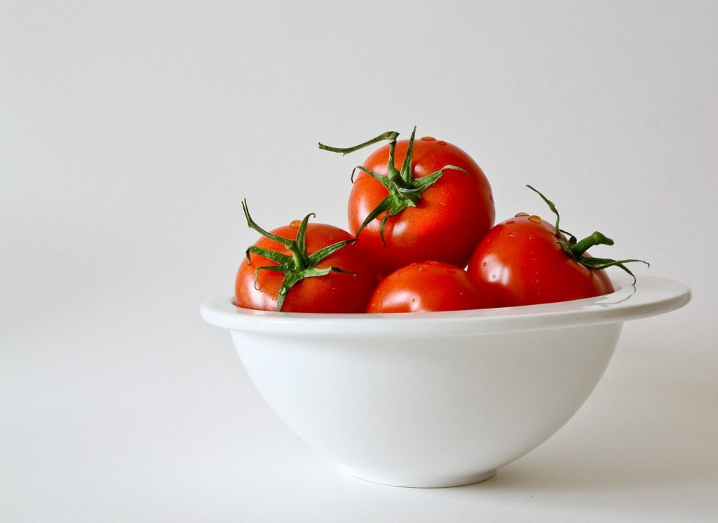 Whole heirloom tomatoes in a white bowl.