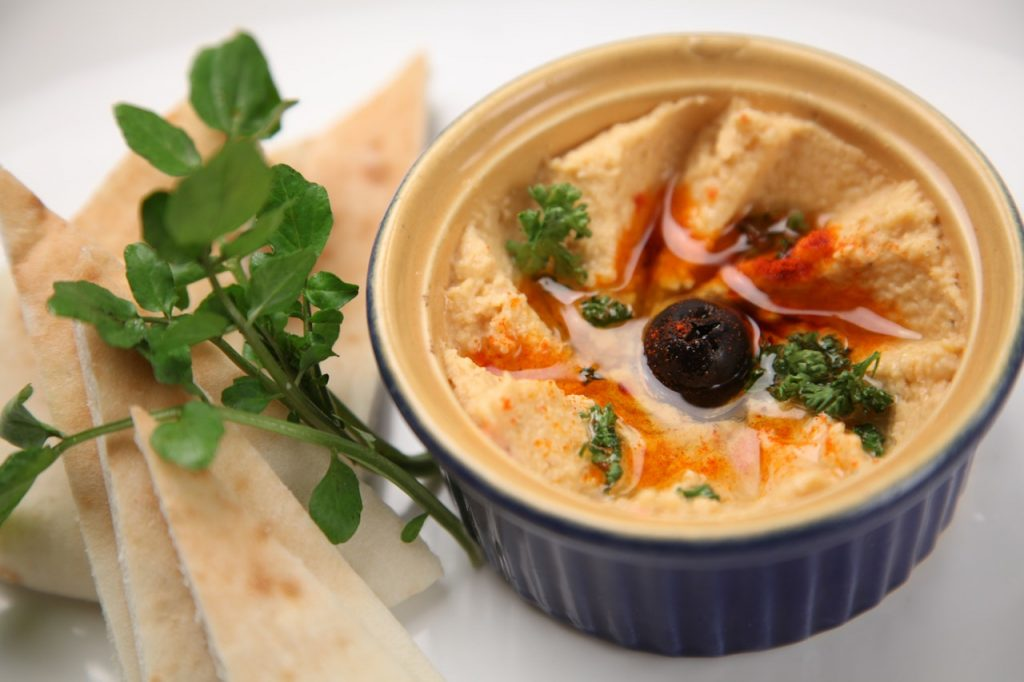Hummus in a bowl, topped with olive oil, paprika, and an olive.