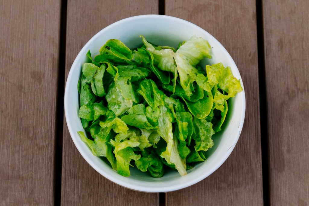 Bowl of salad greens on wooden table.