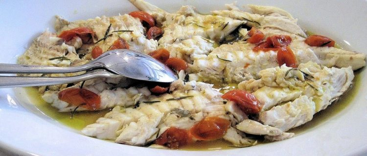 Cooked white fish in a tomato olive oil sauce on a plate with spoon beside it.