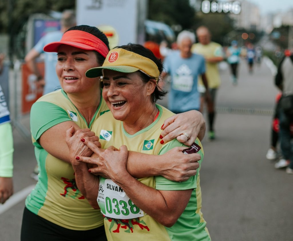 Two older women embrace after running a road race.