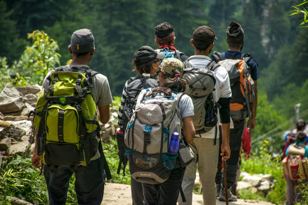 Group of 6 hikers wearing filled backpacks, walking outdoors in dense forest.