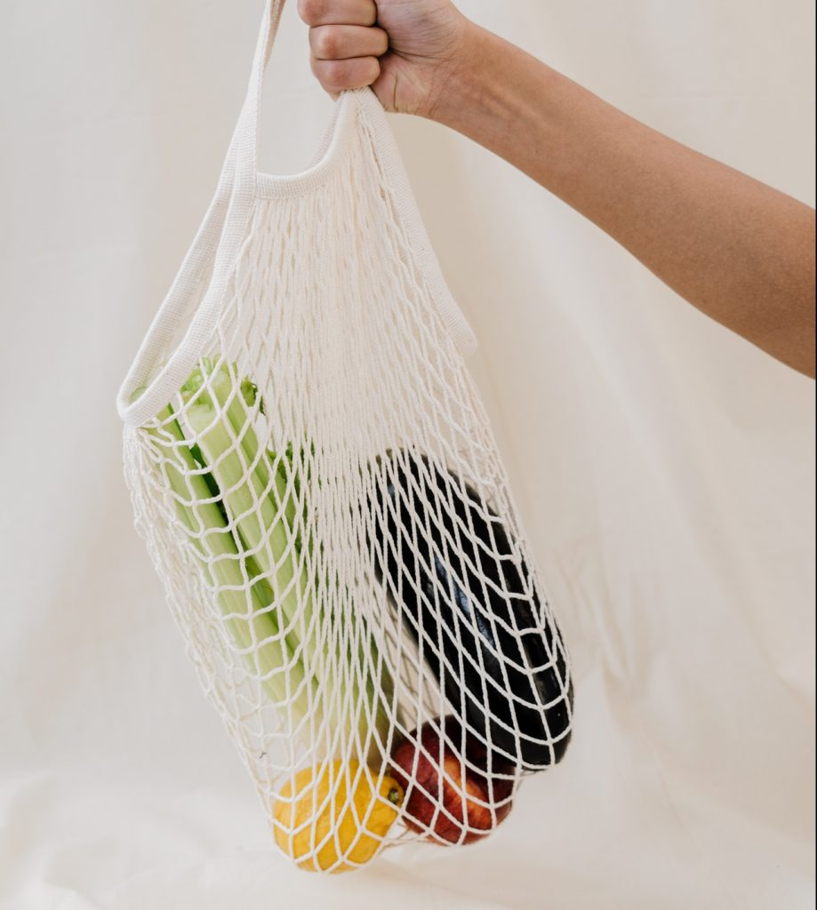 person holding knit reusable grocery bag.