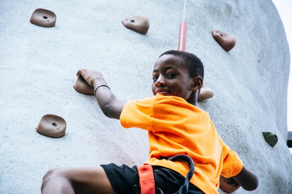 Young boy rock climbing on man-made rock wall.