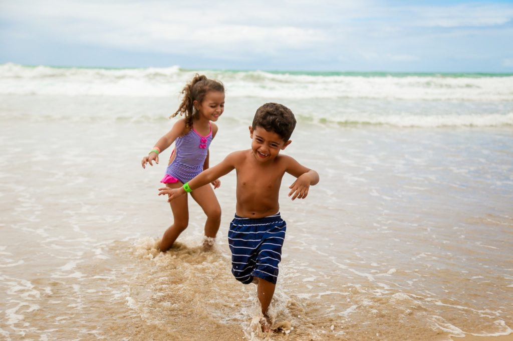 Two young children running out of the ocean.