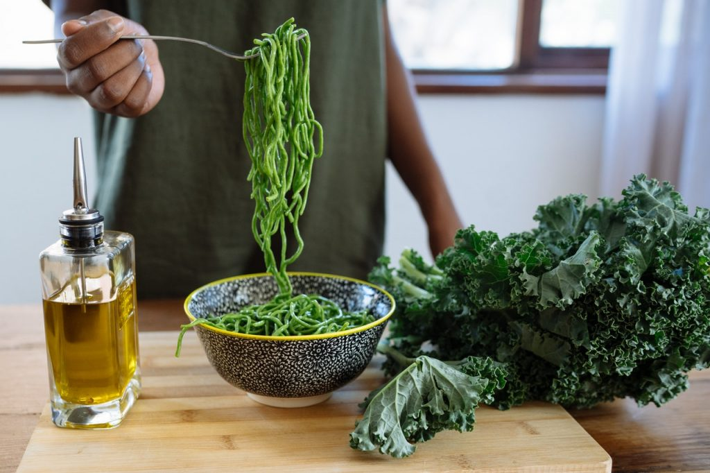 Man holding green pasta up by a fork with olive oil on the side. Kale is beside the cutting board