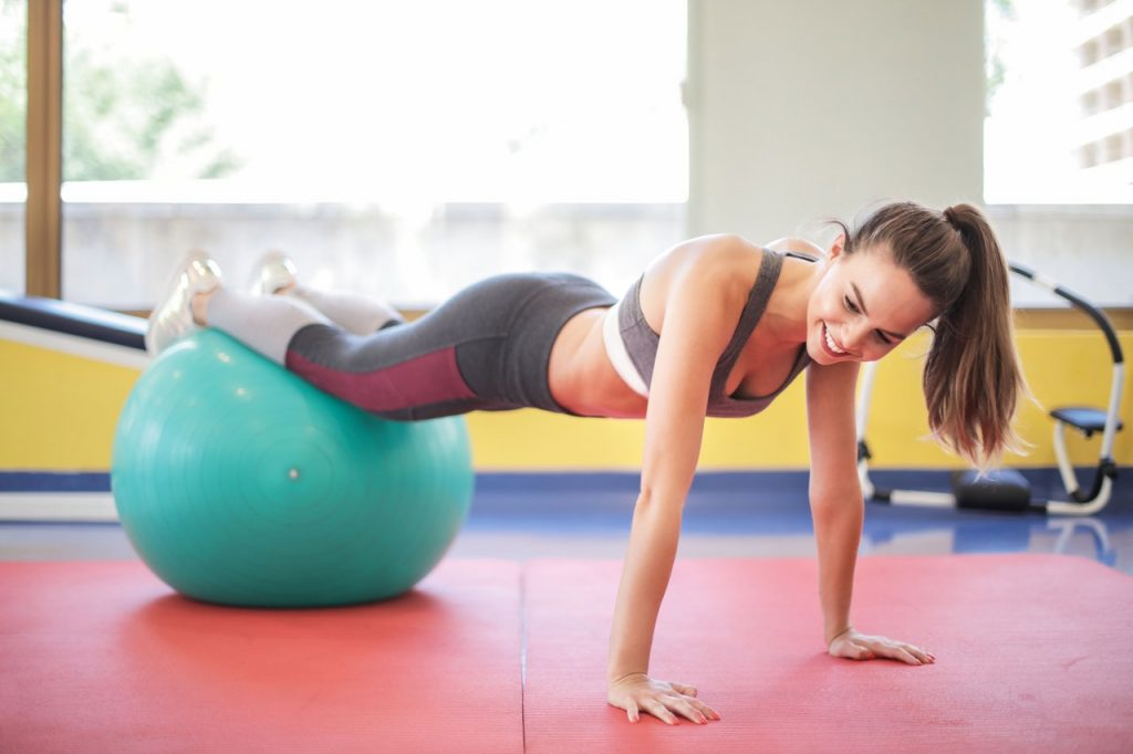 Woman with feet up on stability ball, in the push-up position.