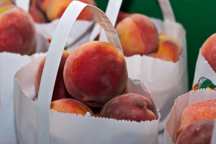 Fresh peaches in paper bags outside.