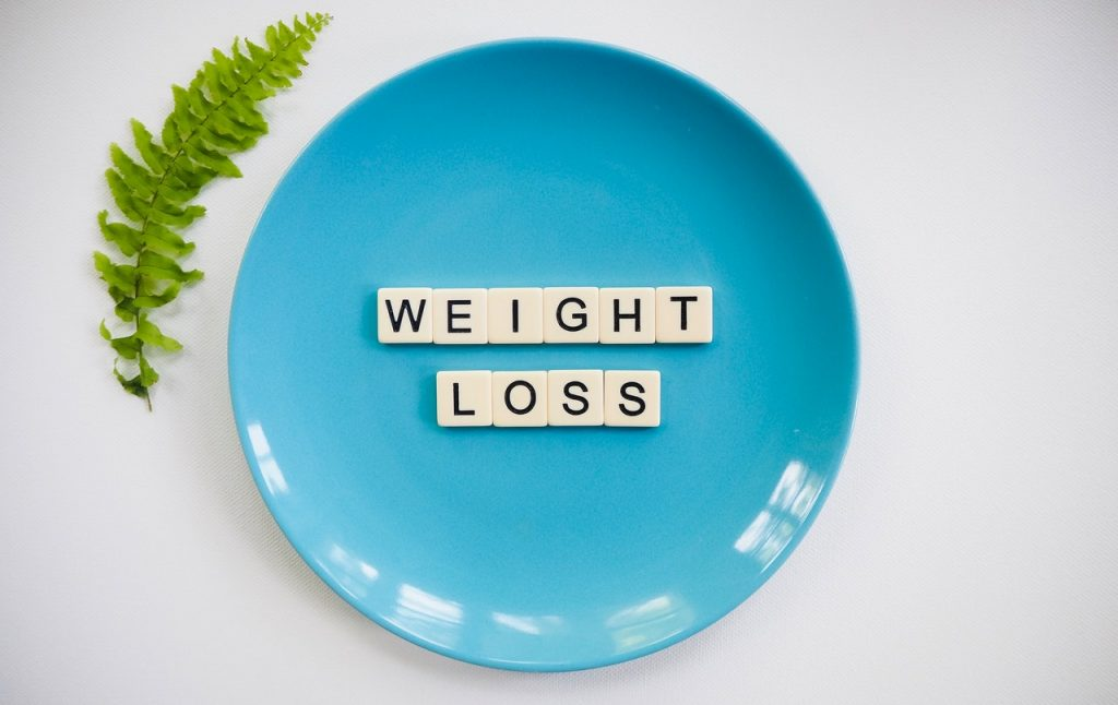 "A blue plate with scrabble letters spelling ""weight loss"""