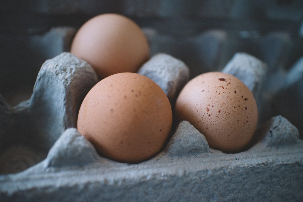 Three brown eggs in cardboard carton.