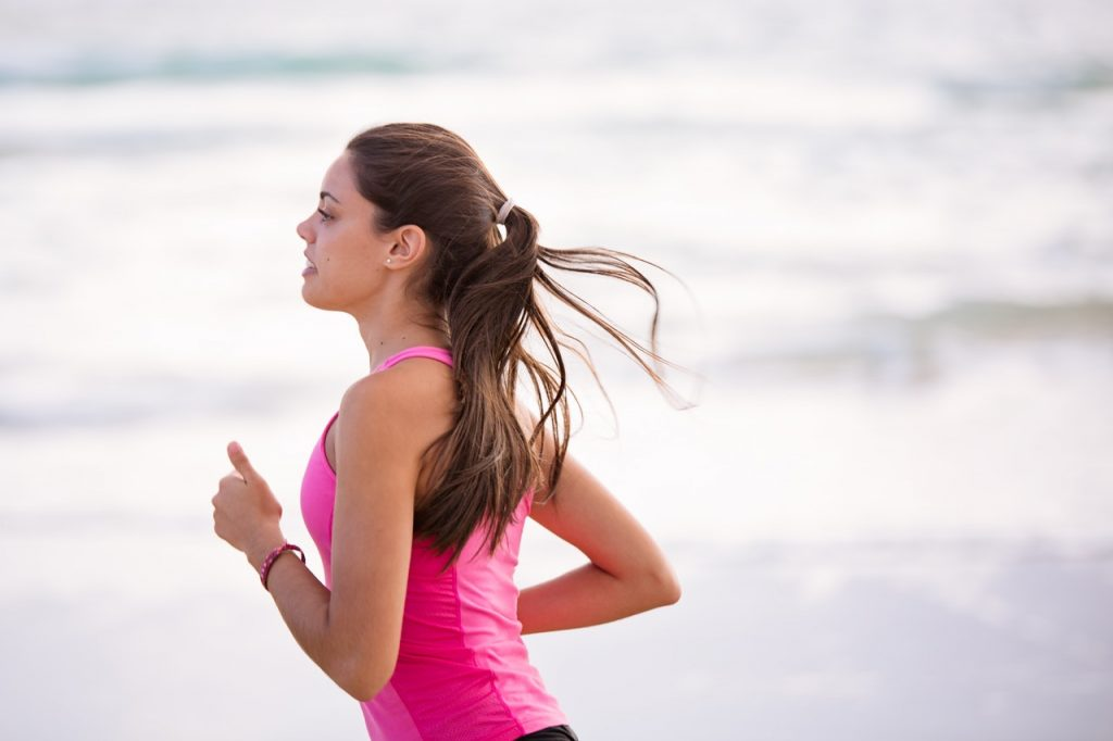 Young woman running on beach in pink tank top, ocean waves visible behind her.