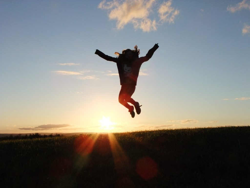 Woman jumping above corn field while sun is setting.