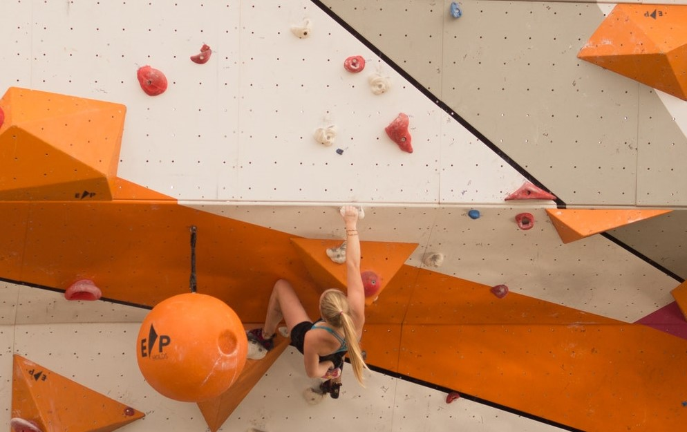 Woman rock climbing at indoor gym.