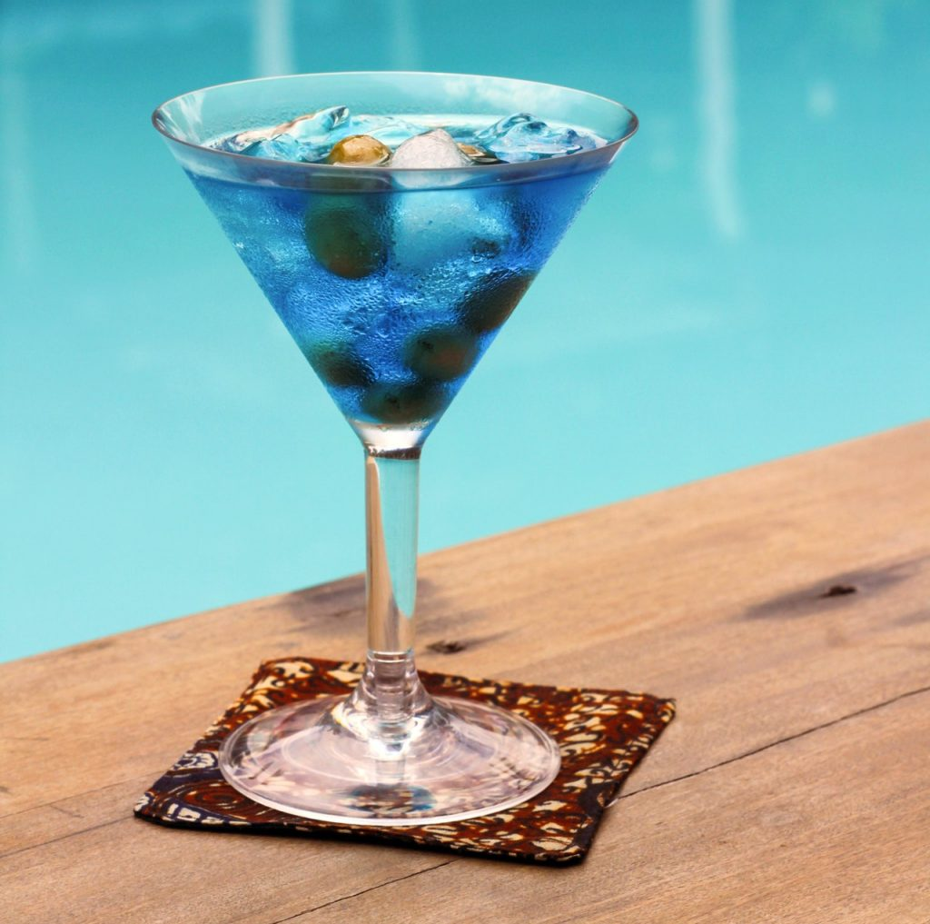 lue colored cocktail with olives on a wooden table next to a pool