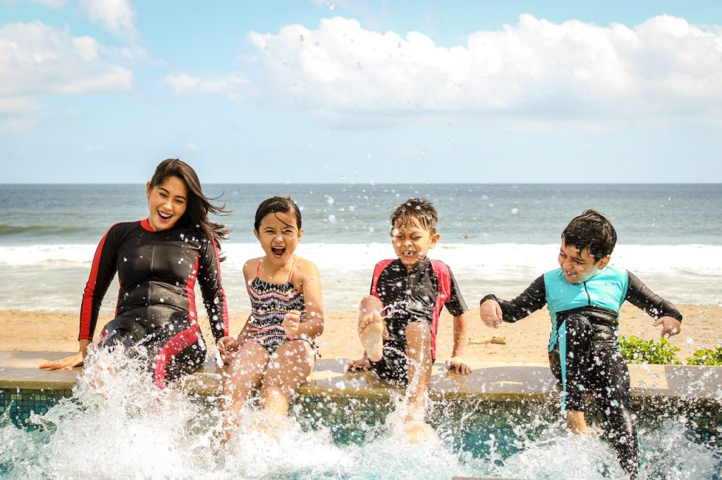 Mother and three children splash their feet in a pool beside the ocean together.