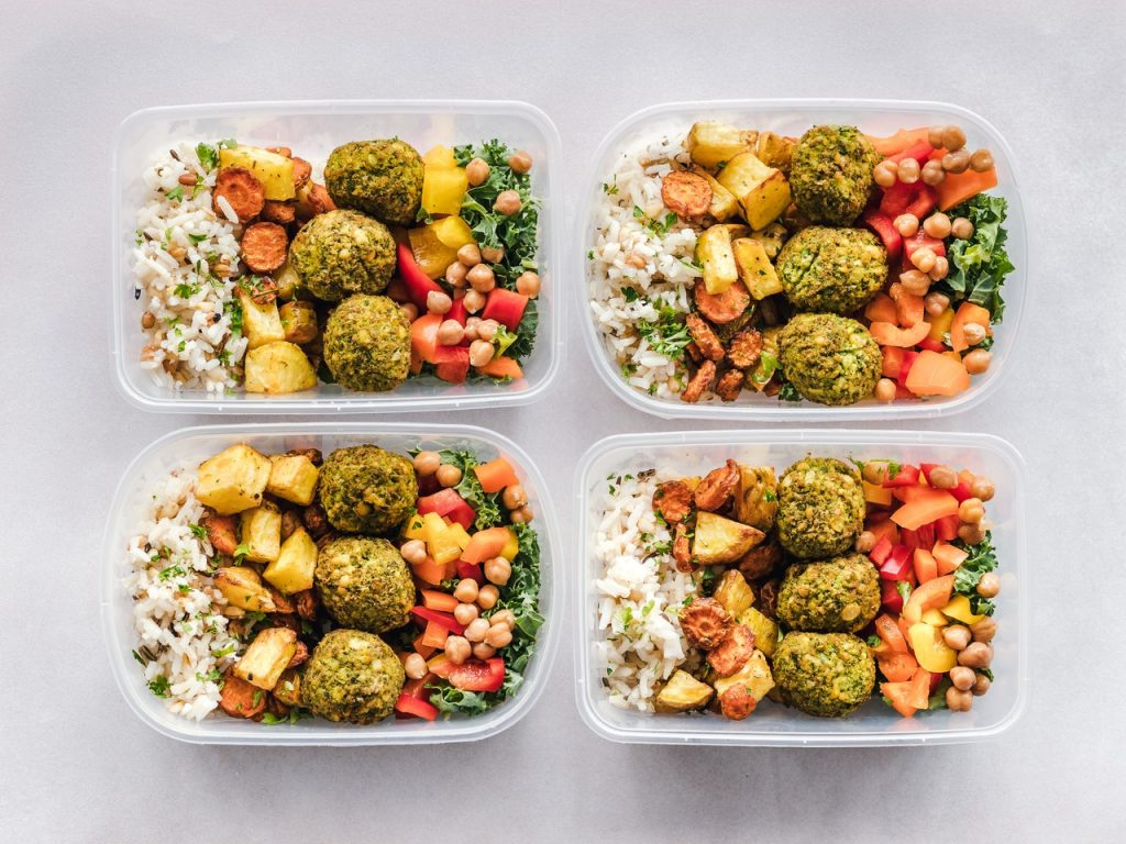 Four Tupperware boxes with rice, carrots, potatoes, falafel, chickpeas, kale and sweet peppers.
