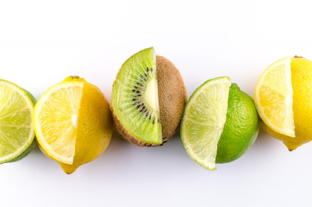 Cut lemon, lime and kiwi next to full lemon, lime and kiwis.