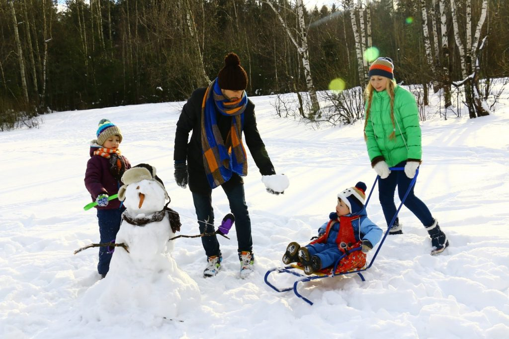 Family playing outside in the snow, building a snow man together