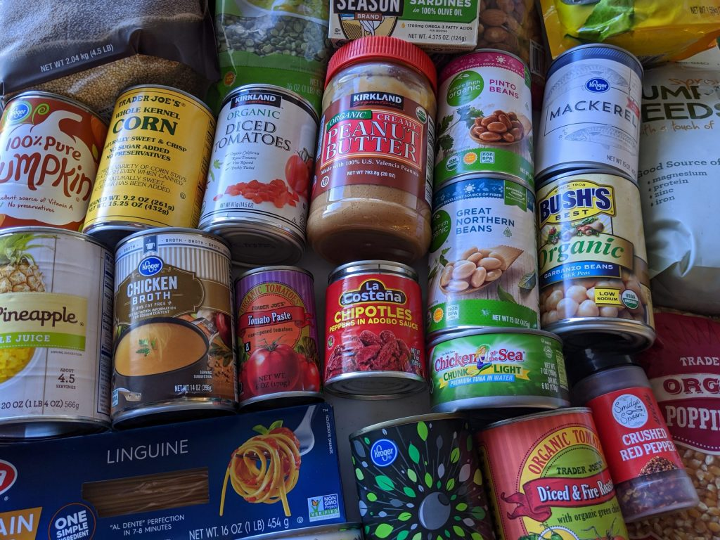 Various shelf-stable foods on table top, including peanut butter, chicken broth, pasta, crushed red pepper and beans.