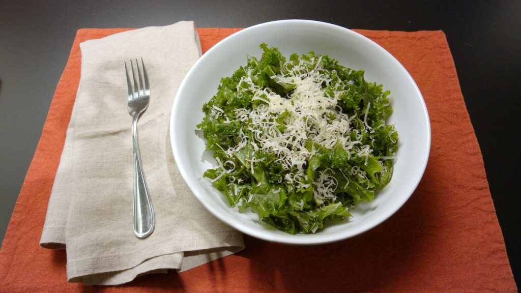 Massaged kale salad topped with shredded parmesan.