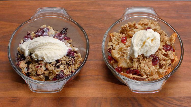 Two individual fruit crisps, including a blueberry crisp and an apple/cranberry crisp.
