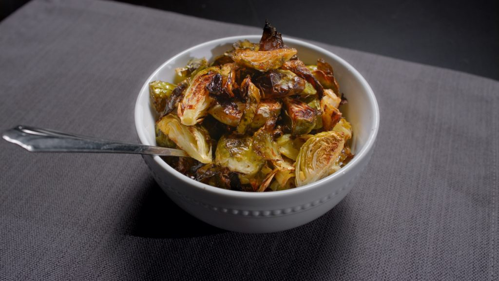 Crispy brussel sprouts in bowl with spoon.