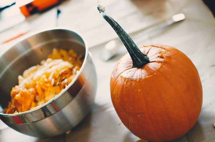 pumpkin pulp in a bowl next to whole pumpkin