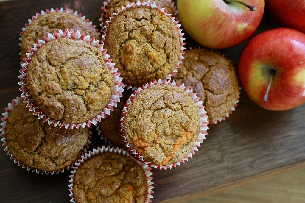 apple muffins cooling on table next to fresh apples.