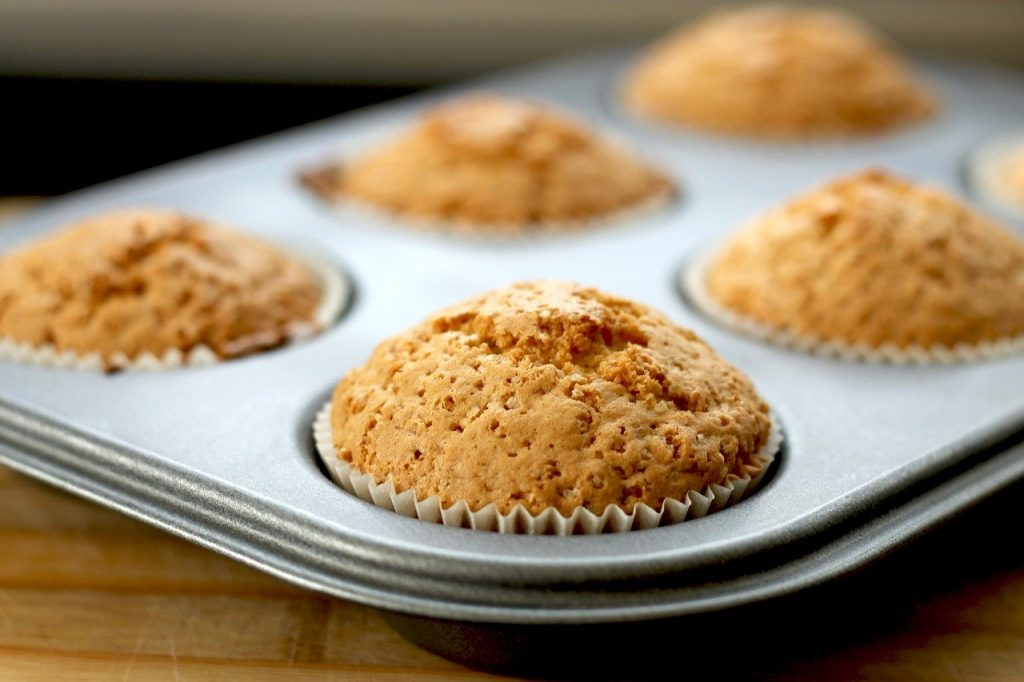 Cooked pumpkin muffins cooling in a tin.