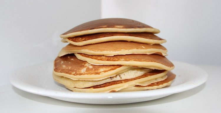 Pancakes on white plate stacked 8 pancakes high.