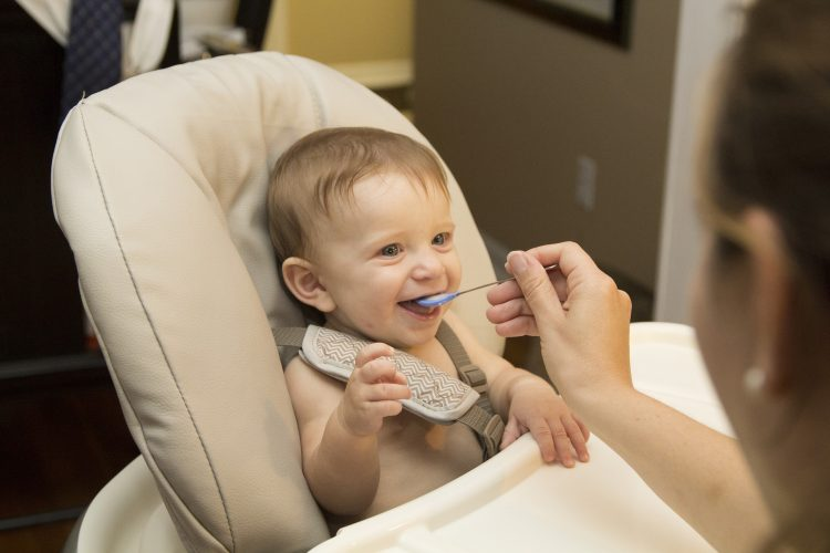 Baby being fed with a spoon while sitting in high chair