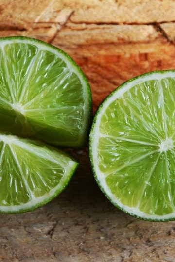 Lime cut in half, and then in quarters, on wood cutting board.
