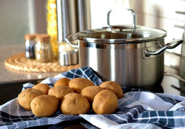 Potatoes, uncooked, on towel next to the stove top.