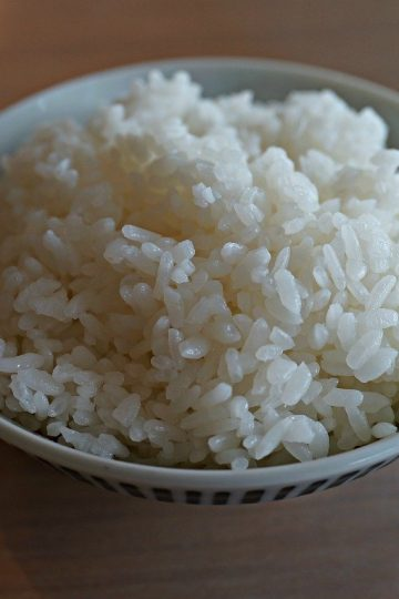 Cooked white rice in small bowl on table.