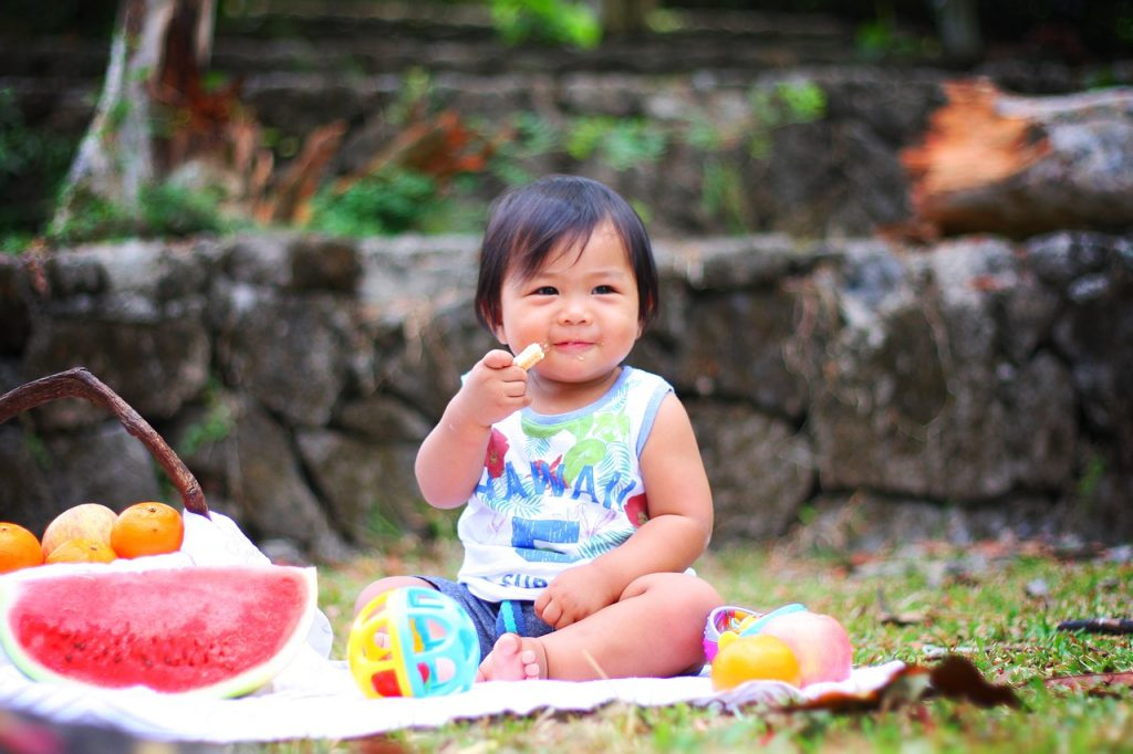 Toddler eating snack outside